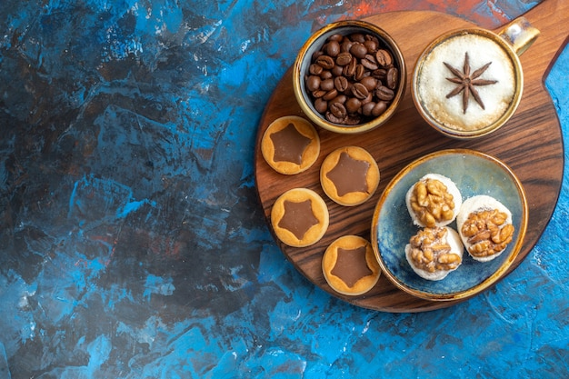 Vista de cima em close-up, biscoitos, biscoitos, delicias turcas, grãos de café, uma xícara de café na placa de madeira