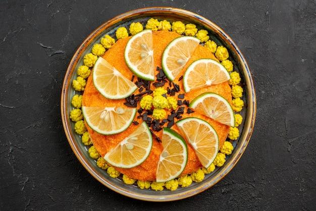 Vista de cima em close-up bolo apetitoso bolo apetitoso com frutas cítricas no prato cinza sobre a mesa escura