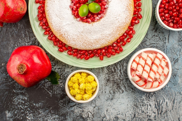 Vista de cima em close-up bolo de doces um bolo duas tigelas de romãs com doces coloridos