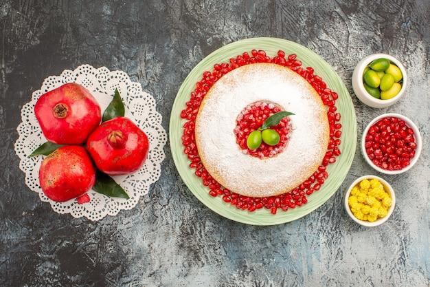 Vista de cima em close-up bolo e doces um bolo frutas cítricas doces romãs no guardanapo de renda