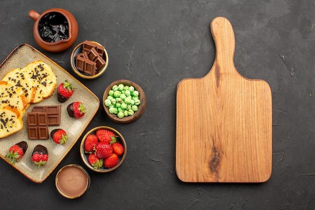 Vista de cima em close-up bolo e morango prato de bolo e tigelas de chocolate, morangos, doces verdes e creme de chocolate ao lado da mesa da cozinha