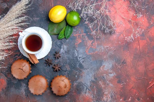 Vista de cima em close-up bolo os bolinhos apetitosos uma xícara de chá frutas cítricas com folhas