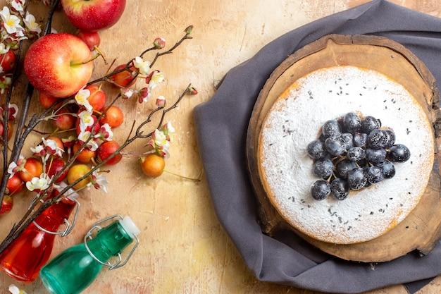 Vista de cima em close-up bolo um bolo com uvas, cereja, maçãs, ramos de árvore com garrafas de flores