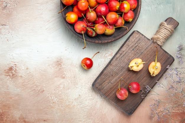Vista de cima em close-up cerejas galhos de árvores cerejas na tigela e no quadro