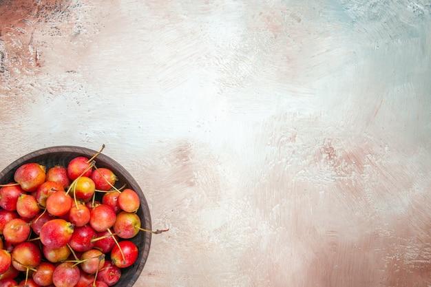 Vista de cima, em close-up, cerejas, tigela marrom de cerejas em cima da mesa