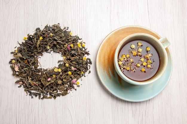 Vista de cima em close-up chá de ervas chá de ervas em uma xícara branca ao lado das ervas no prato branco
