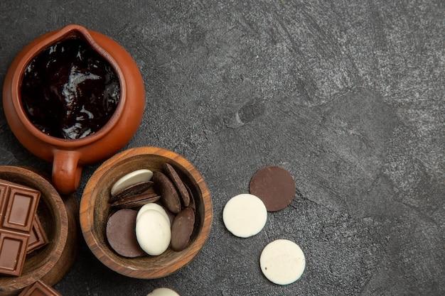 Vista de cima em close-up com calda de chocolate nas tigelas pretas da mesa com chocolate e calda de chocolate