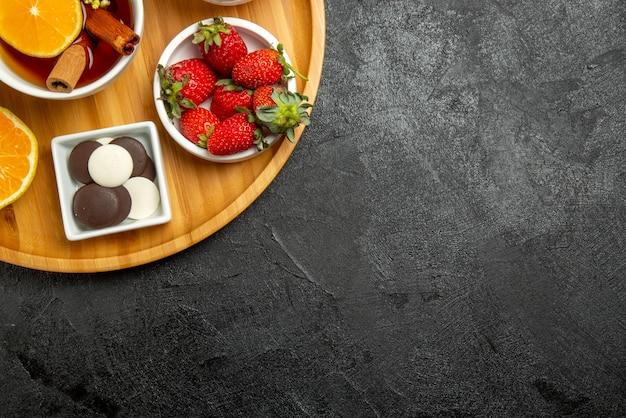 Vista de cima em close-up com chocolate limão taças de morangos com chocolate uma xícara de chá com palitos de cinnabon e limão no lado esquerdo da mesa