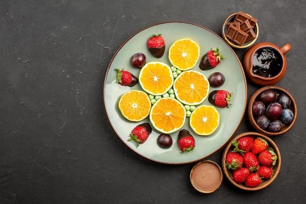 Vista de cima em close-up com frutas de chocolate tigelas de madeira com morangos, frutas de chocolate e calda de chocolate ao lado de um prato branco com morangos de laranja picados no lado direito da mesa escura