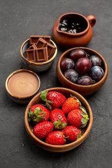 Vista de cima em close-up com frutas de chocolate tigelas de madeira com morangos, frutas de chocolate e calda de chocolate no centro da mesa escura