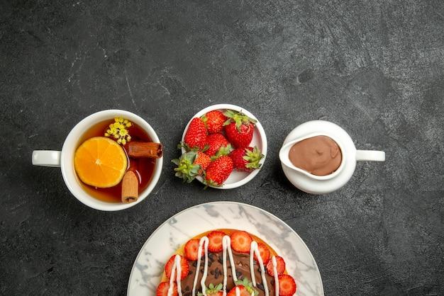 Vista de cima em close-up com morango com chocolate, bolo apetitoso e uma xícara de chá com limão e canela ao lado das tigelas de morango e creme de chocolate na mesa escura