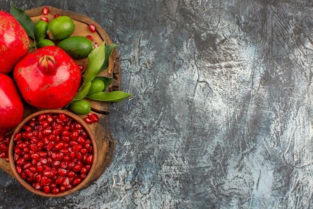 Vista de cima em close-up com sementes de romã e três romãs na mesa da cozinha