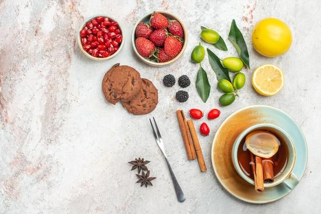 Vista de cima em close-up cookies de chocolate cookies de chocolate uma xícara de chá com limão e paus de canela garfo tigelas de frutas cítricas romã na mesa