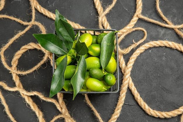 Vista de cima em close-up corda de frutas cítricas ao lado das frutas na cesta