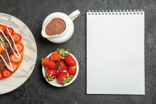 Vista de cima em close-up, creme de chocolate, morangos, bolo apetitoso com frutas, caderno branco, tigelas de morangos e creme de chocolate na mesa