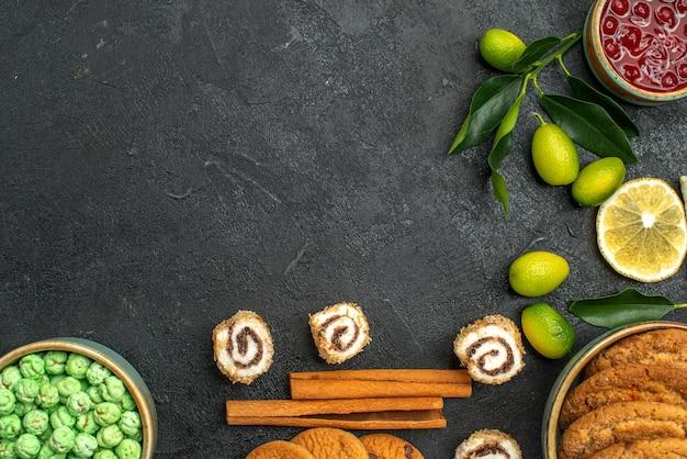 Vista de cima em close-up doces geleia biscoitos doces verdes canela frutas cítricas na mesa