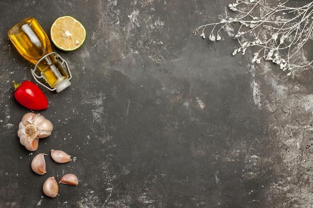 Vista de cima em close-up especiarias garrafa de pimenta vermelha de óleo de limão e alho ao lado dos galhos da árvore na mesa escura