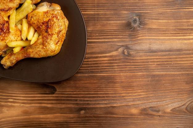 Vista de cima em close-up fast food apetitosas batatas fritas e frango no prato marrom na mesa de madeira