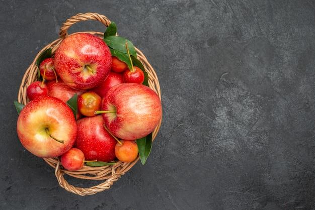 Vista de cima em close-up, frutas, cerejas e maçãs na cesta na mesa escura