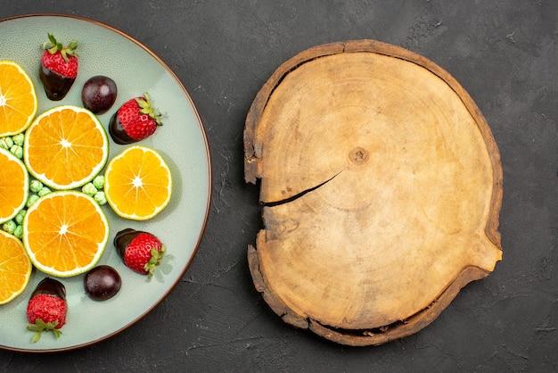 Vista de cima em close-up frutas e chocolate picado laranja e morangos cobertos de chocolate e doces verdes ao lado da placa de cozinha de madeira na mesa preta