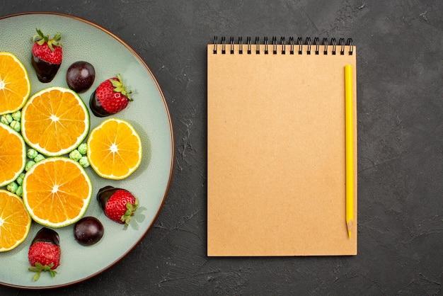 Vista de cima em close-up frutas e chocolate picado laranja e morangos cobertos de chocolate e doces verdes ao lado do caderno creme e lápis amarelo na mesa preta