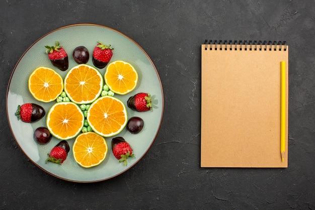 Vista de cima em close-up frutas e laranja picada de chocolate com morangos cobertos de chocolate e doces verdes ao lado do caderno de creme e lápis amarelo na mesa escura