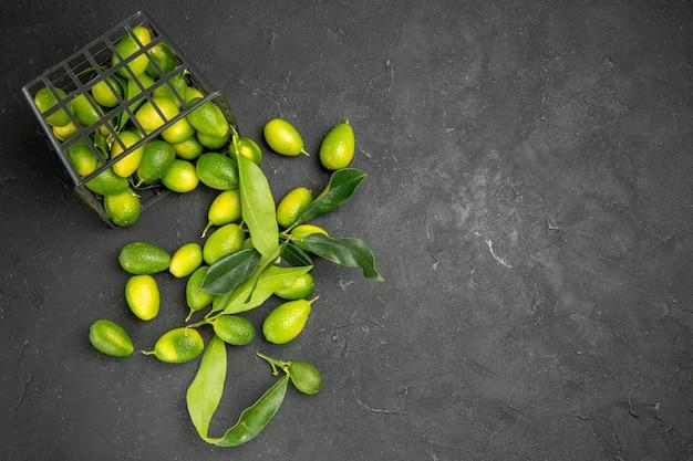 Vista de cima em close-up frutas frutas cítricas com folhas ao lado da cesta com frutas na mesa