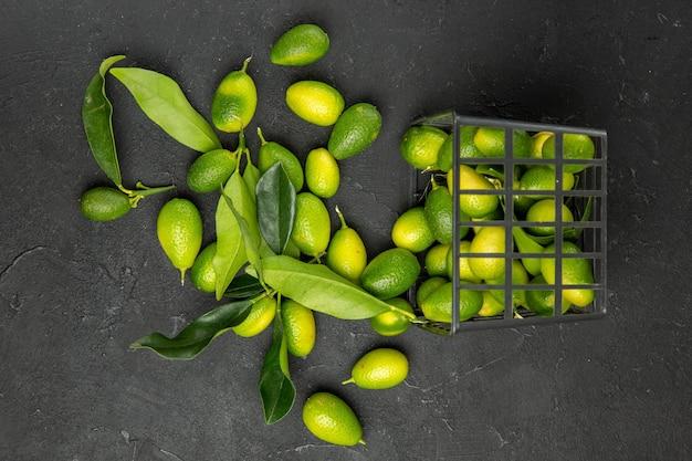 Vista de cima em close-up frutas frutas cítricas com folhas ao lado da cesta