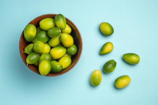 Vista de cima em close-up frutas frutas verdes em uma tigela ao lado das frutas