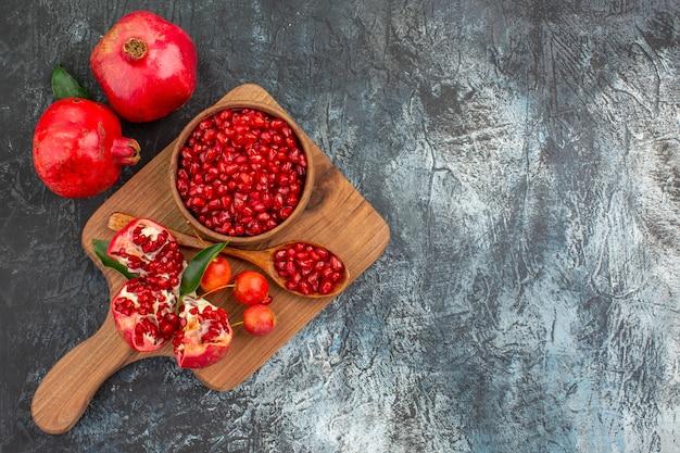 Vista de cima em close-up frutas no tabuleiro com sementes de romã colher cerejas de romã descascadas