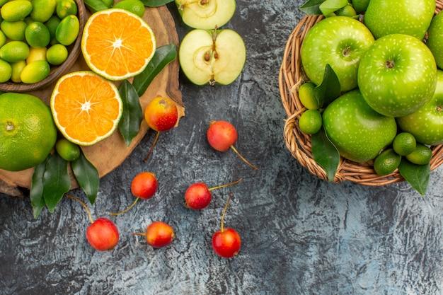 Vista de cima em close-up frutas tangerinas laranjas cerejas na cesta de maçãs