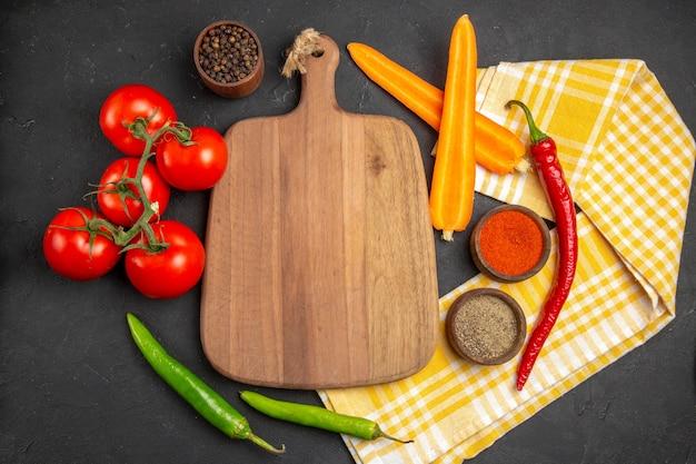 Vista de cima em close-up legumes a tábua de cortar toalha de mesa cenouras pimentas temperadas tomates