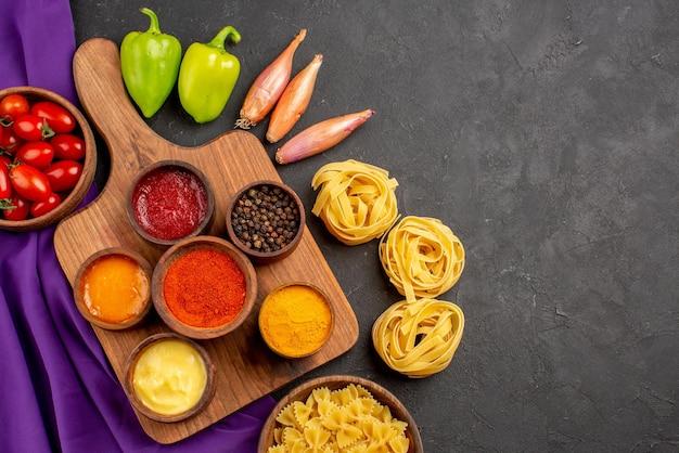 Vista de cima em close-up macarrão e tomate temperos e molhos em tigelas na tábua bola pimenta cebola tigela de tomates e macarrão na toalha roxa sobre a mesa