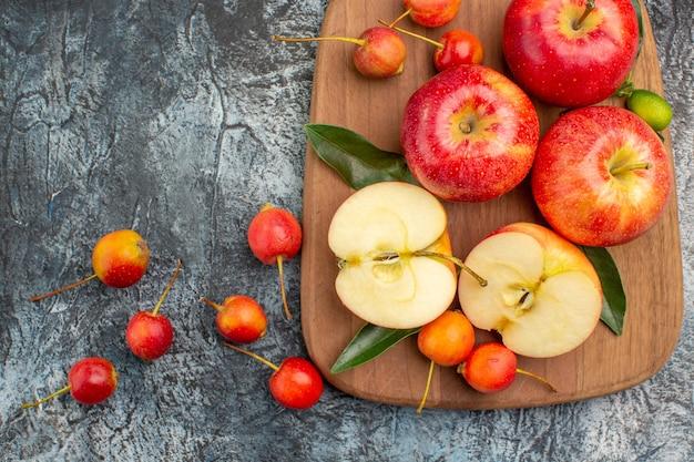 Vista de cima em close-up maçãs maçãs vermelhas cerejas na tábua