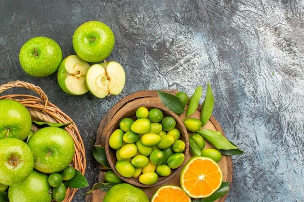 Vista de cima em close-up maçãs no tabuleiro com diferentes frutas cítricas cesta de frutas cítricas maçãs