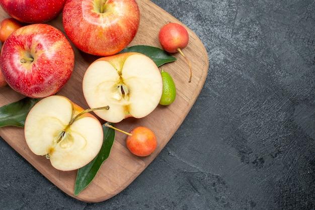 Vista de cima em close-up, maçãs, tábua de cortar cerejas, maçãs, frutas cítricas