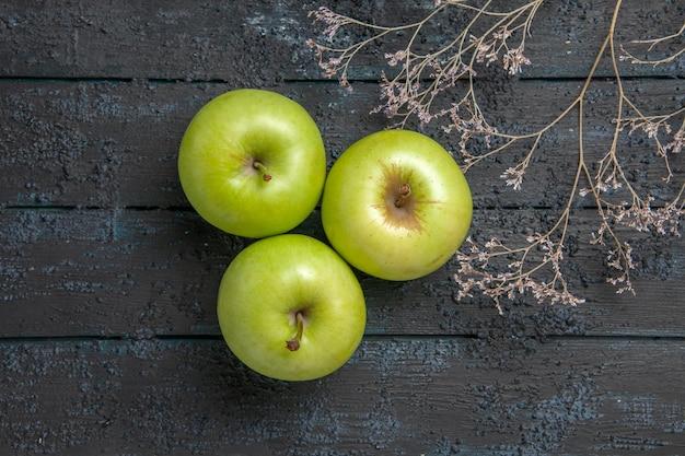 Vista de cima em close-up maçãs verdes três maçãs apetitosas ao lado de galhos de árvores no centro da mesa cinza