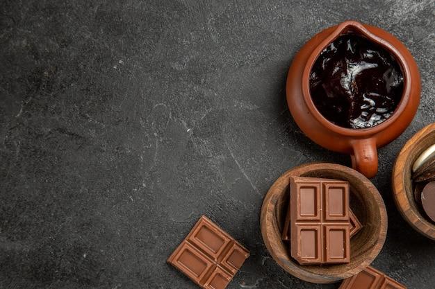 Vista de cima, em close-up, molho de chocolate no lado direito da mesa preta, tigelas marrons de chocolate e molho de chocolate