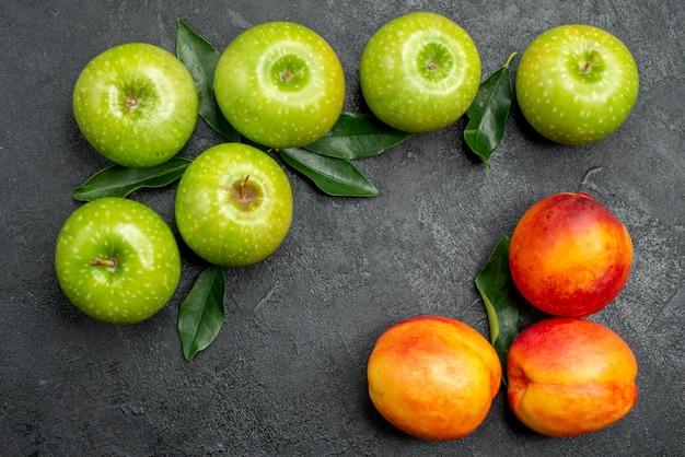 Vista de cima em close-up nectarinas maçãs, três nectarinas e seis maçãs com folhas na mesa