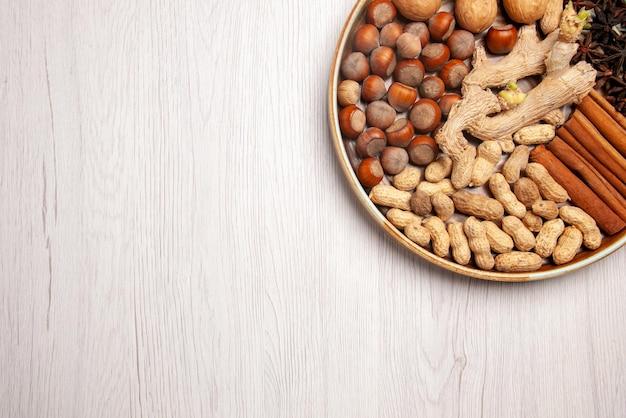 Vista de cima em close-up nozes apetitosas avelãs, nozes, amendoim, paus de canela e anis estrelado no lado esquerdo da mesa