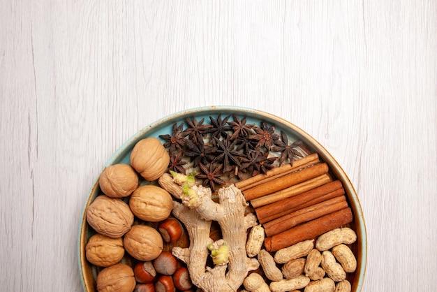 Vista de cima em close-up, nozes, avelãs, nozes, amendoim, canela e anis estrelado na mesa