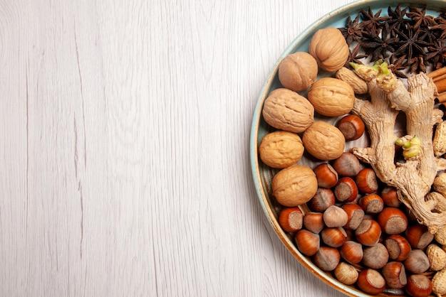 Vista de cima em close-up, nozes, avelãs, nozes, amendoim, paus de canela e anis estrelado na mesa
