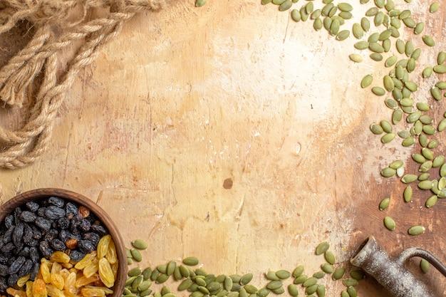 Vista de cima em close-up passas passas na tigela ao lado da corda de sementes de abóbora