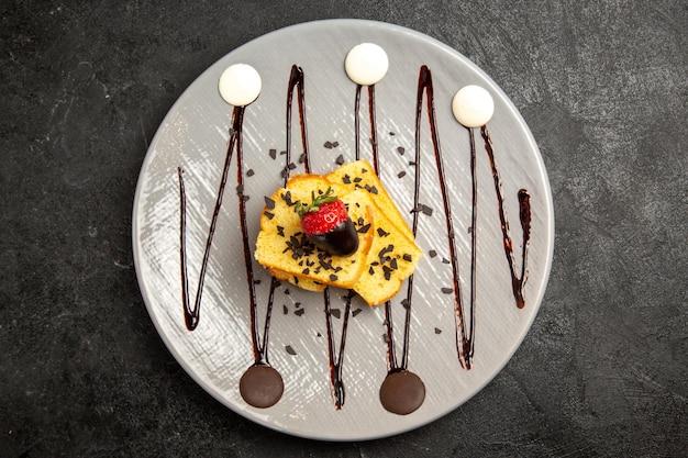 Vista de cima em close-up, pedaços de bolo de sobremesa com morangos cobertos de chocolate e calda de chocolate no prato cinza sobre a mesa escura