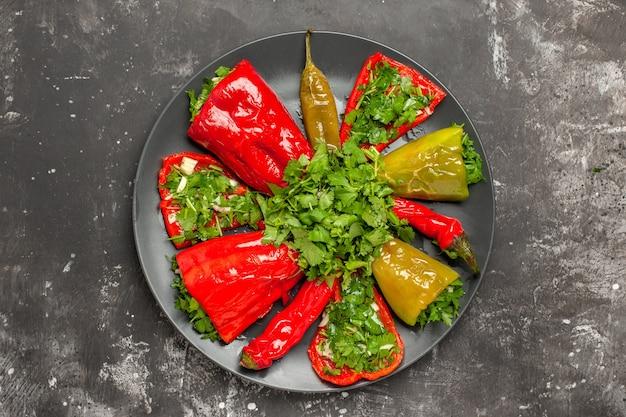 Vista de cima em close-up pimenta colorida de diferentes tipos de pimentas com ervas na placa preta