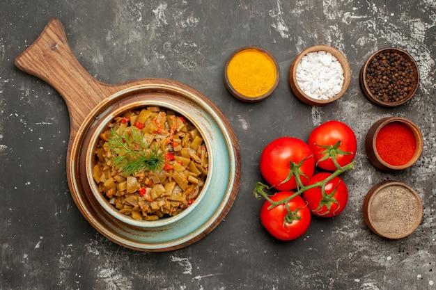 Vista de cima em close-up prato apetitoso prato apetitoso ao lado de tigelas de temperos coloridos na mesa escura