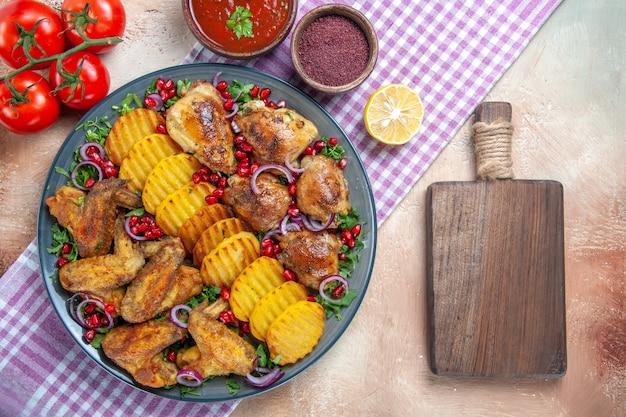Vista de cima em close-up prato asas de frango batatas molho tomate temperos a tábua