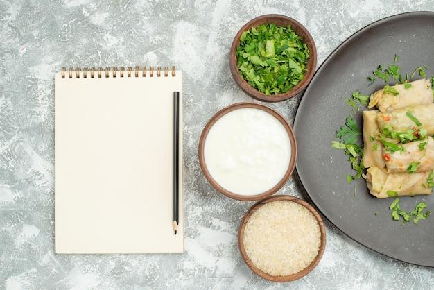 Vista de cima em close-up prato com prato de ervas de repolho recheado ao lado de tigelas de arroz de creme azedo de ervas ao lado de caderno branco e lápis na mesa
