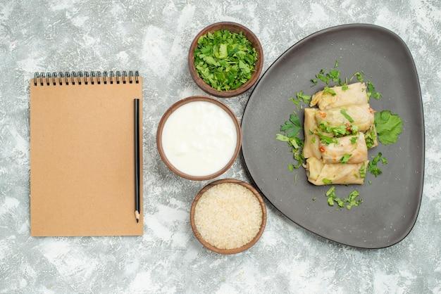 Vista de cima em close-up prato com prato de ervas de repolho recheado ao lado de tigelas de arroz de creme azedo de ervas ao lado de caderno de creme e lápis na mesa