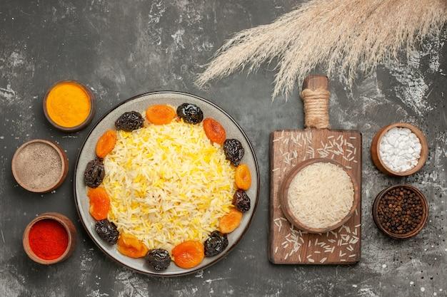 Vista de cima em close-up prato de arroz com frutas secas e uma placa de madeira com uma tigela de especiarias de arroz